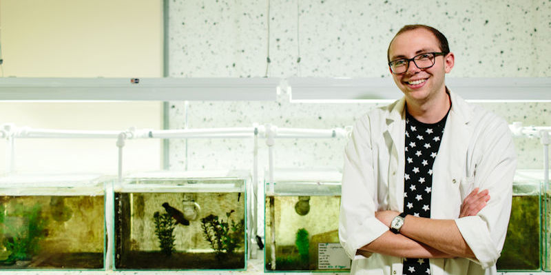 A Biological Sciences student standing in front of fish tanks in a lab.
