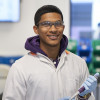 Image of a male undergraduate student standing in a laboratory. He is wearing a white lab coat with a yellow collar over a purple hoody. He is also wearing blue gloves and holding a piece of equipment. He is looking directly at the camera and smiling.