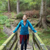 This image shows a woman standing on a wooden bridge in the middle of a forest. She is smiling.