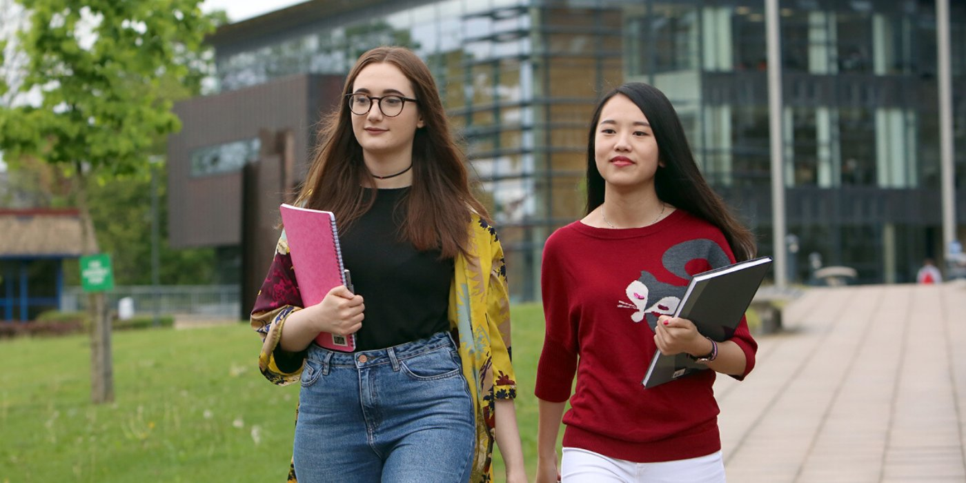 two female students, walking through campus