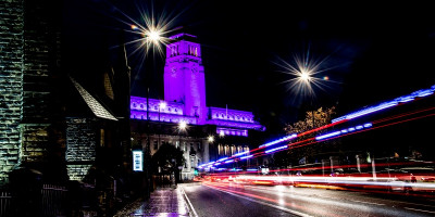 An image of the University of Leeds Parkinson building illuminated in purple light.